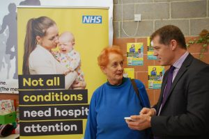 """Dr Mark Wells, Clinical Lead for Urgent Care, shows patient Margaret Jeffries the new Health Help Now app"""
