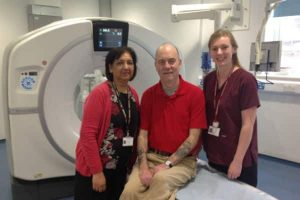 Wallace-Sharpless-centre-the-first-patient-to-use-the-new-CT-scanner-next-to-Mina-Deved-Head-of-Radiology-Services-left-and-Senior-Radiographer-Louisa-Andrews-right